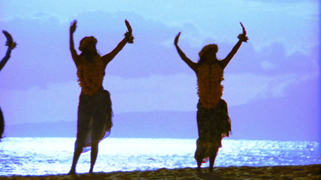 pan silhouettes of three female hula dancers dancing in unison / ocean in background / hawaii - hawaiian culture stock videos & royalty-free footage