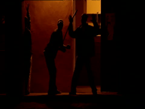 vídeos de stock, filmes e b-roll de silhouettes of three men dancing in doorway to shebeen in orange evening light - estilo dos anos 2000