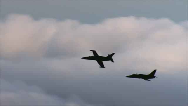 air to air, silhouettes of two aero l-39 albatroses flying against sky - air force stock videos & royalty-free footage
