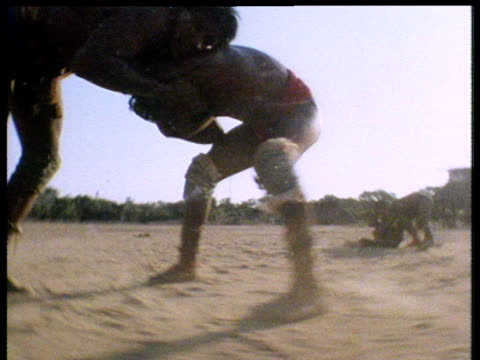 silhouettes of two amazonian indian men in traditional dress wrestling with each other on sandy ground sunflare bursts through intermittently - wrestling stock videos and b-roll footage