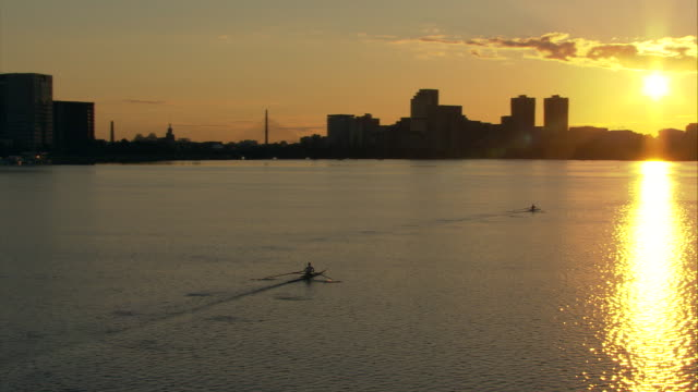 WS Silhouettes of two crew boats moving across Charles River at sunrise, city skyline in background / Boston, Massachusetts, USA