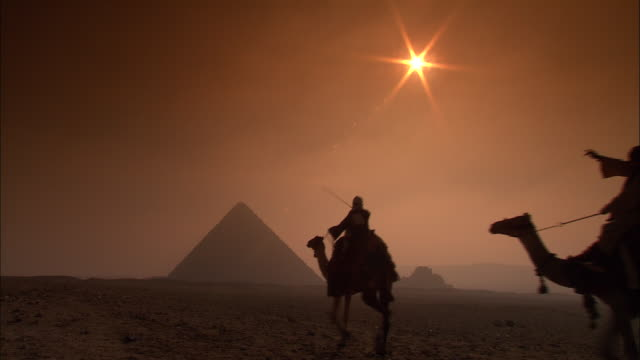 WS, Silhouettes of two people riding camels at sunset, Giza Pyramids in background, rear view, Giza Plateau / Giza, Egypt