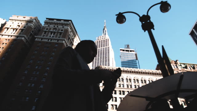 Silhouettes of unrecognizable people walking by New York City's Empire State Building