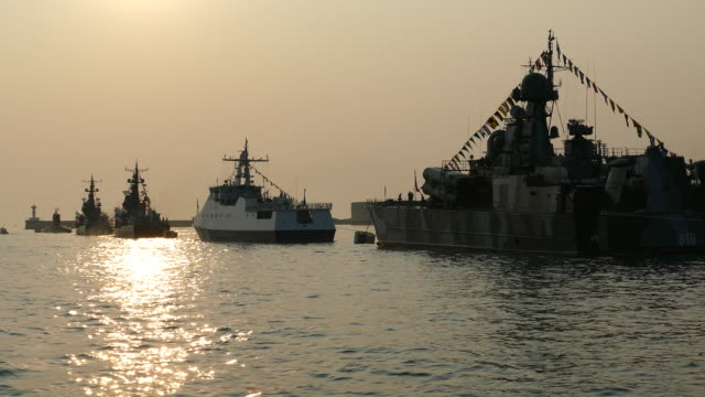 silhouettes of warships at sunset