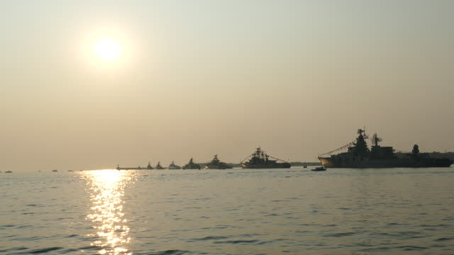 silhouettes of warships on the background of the sun