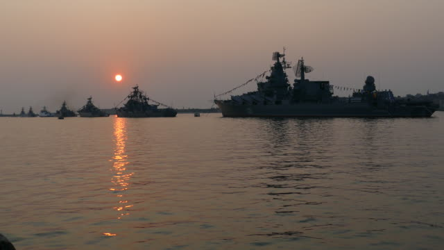 silhouettes of warships on the evening sea