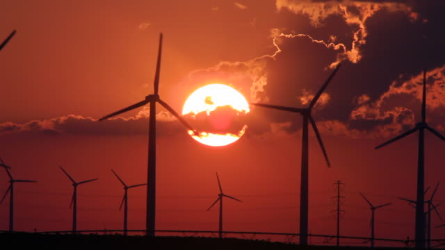vídeos y material grabado en eventos de stock de silhouettes of wind turbines against an orange sky at sunset - texas