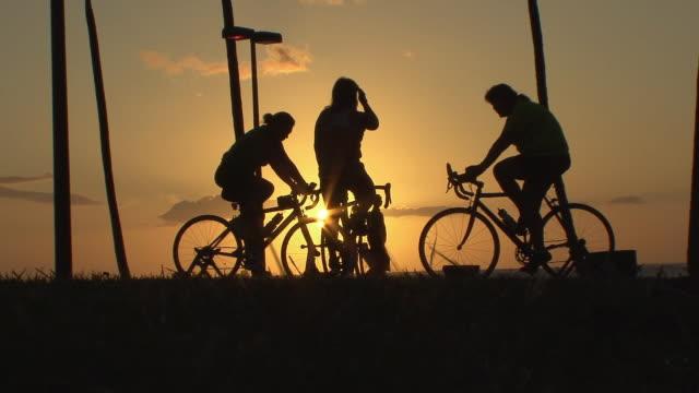 WS Silhouettes of women on bikes against setting sun on Waikiki Beach / Honolulu, Hawaii, USA