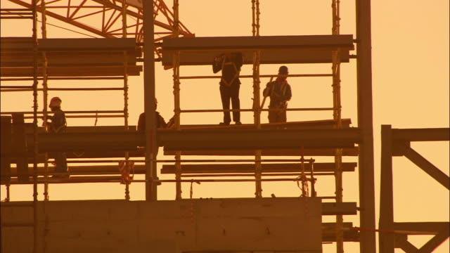vídeos de stock e filmes b-roll de ms silhouettes of workers on construction site at sunrise, dubai, united arab emirates - andaime