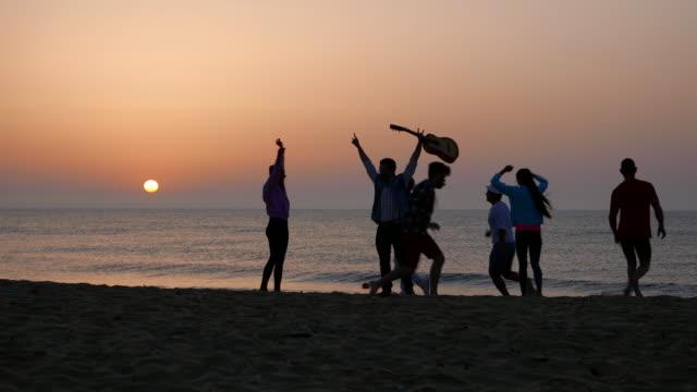 vídeos de stock, filmes e b-roll de silhuetas na praia ao nascer do sol - violão