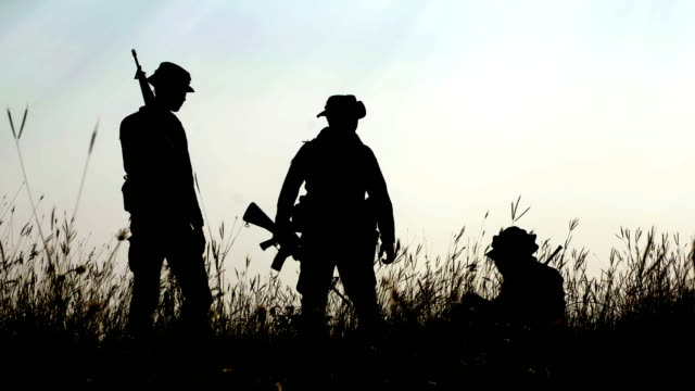 Silhouettes,Squad of Three Fully Equipped and Armed Soldiers Standing in forest Environment in Sunset Light.Soldiers bring water to their friends, drink and pull their hands up.