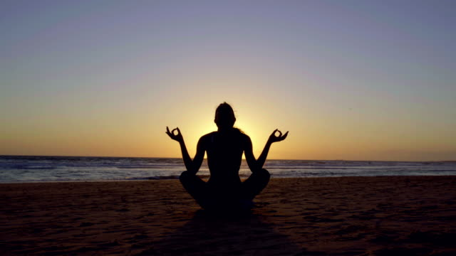 silhoutte of beautiful woman making yoga in the beach at sunset - silvestre stock-videos und b-roll-filmmaterial