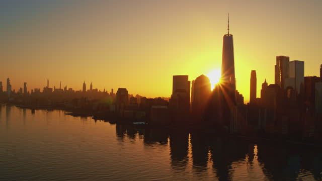 silhuette of manhattan skyline against the rising sun. the view across the hudson river, from jersey city, at the sunrise. aerial footage with the cinematic panoramic camera motion. - world trade center manhattan stock videos & royalty-free footage