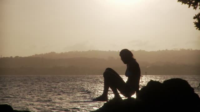 ws sillhouette of young woman sitting down on rock at water's edge during sunset/ scarborough, tobago, trinidad and tobago - trinidad trinidad and tobago stock videos & royalty-free footage