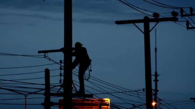 sillouette Elektriker-lineman Handwerker Arbeiter beim Klettern Arbeit an elektronischen post power-pole-Fels