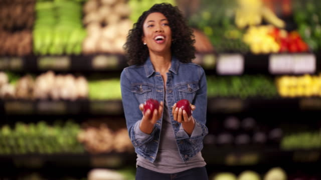silly cute black female juggling apples at grocery store instead of shopping - jonglieren stock-videos und b-roll-filmmaterial