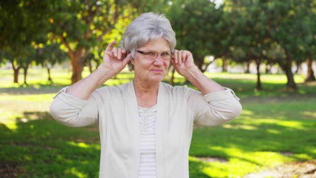 vidéos et rushes de silly senior woman making faces at camera - tongue