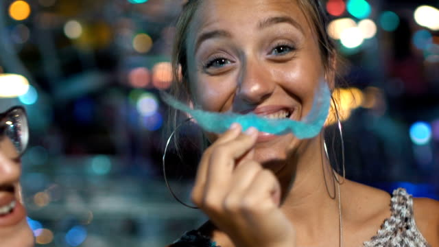 silly teenage girl eats cotton candy - amusement park stock videos & royalty-free footage