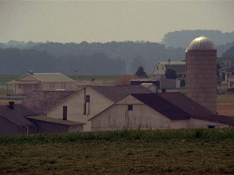stockvideo's en b-roll-footage met a silo stands among farm buildings in amish country. - amish