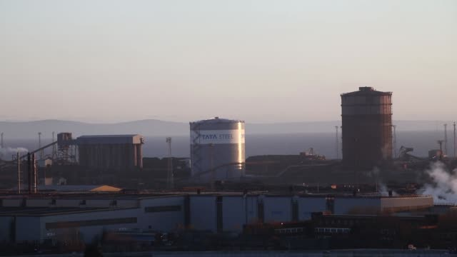 silos stand at the steel works operated by tata steel ltd in port talbot uk on thursday march 31 the sun sets behind the steel works smoke rises from... - downsizing stock videos & royalty-free footage