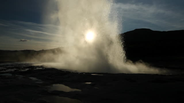 MS Silouette of geothermal steam blowing past Strokkur geyser and geyser erupting in Geysir Park / Haukadalur, Haukadalur, Iceland
