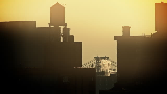a silouette of the williamsburg bridge between two apartment buildings in new york city - lower east side bildbanksvideor och videomaterial från bakom kulisserna