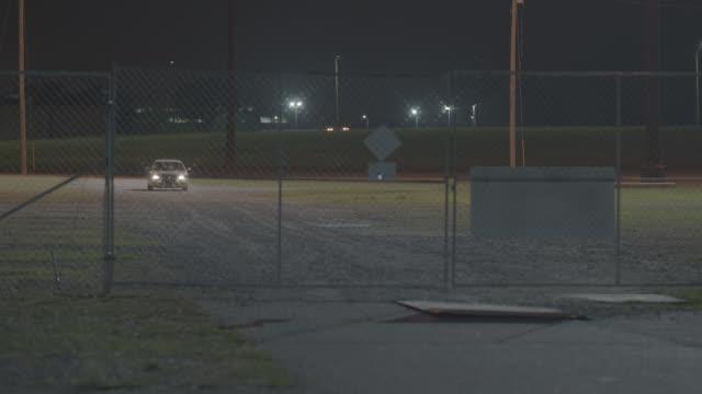silver 2004 dodge stratus 4 door sedan crashes through chain link gates - night - fence stock videos & royalty-free footage