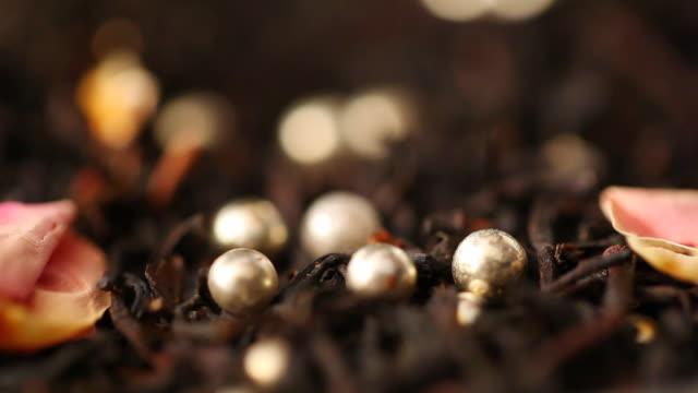vídeos de stock e filmes b-roll de ecu silver bead falling on black tea leaves / seoul, south korea - ingrediente