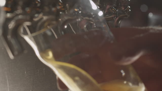 vidéos et rushes de silver beer tap in row fills pint glass - remplir