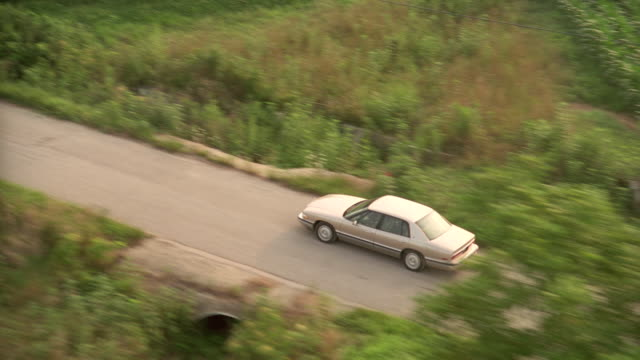 a 1994 silver buick sedan moves along a country road in indiana. - sedan stock videos & royalty-free footage
