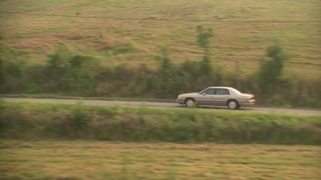a 1994 silver buick sedan moves along a country road past pastures in indiana. - indiana stock videos & royalty-free footage