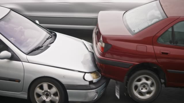 silver car hitting the red car from behind - incidente automobilistico video stock e b–roll