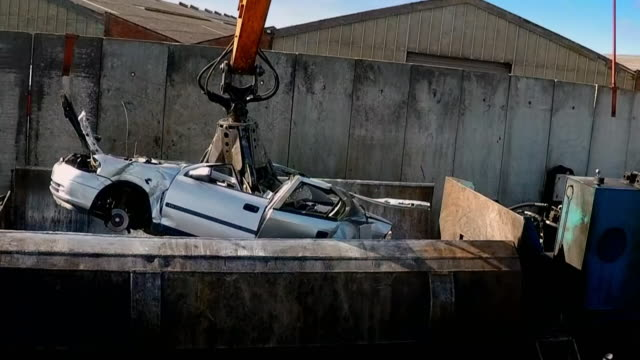 a silver car is crushed at a recycling centre - broken stock videos & royalty-free footage