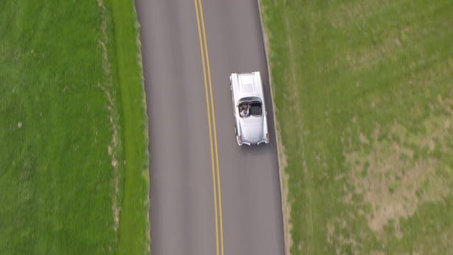 cu aerial ts silver corvette driving on road and other cars passing by / bowling green, kentucky, united states - convertible overhead stock videos & royalty-free footage