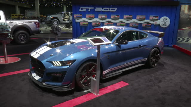 ANGLE silver Mustang up on a giant shelf ZOOM OUT WS front quarter driver side POV blue Mustang on the floor / SAME SHOT DIFFERENT TAKE SLOWER ZOOM /...