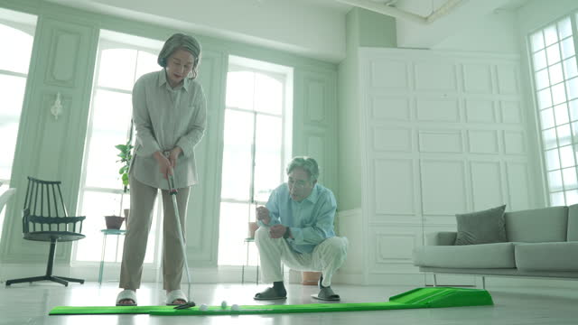 silver surfer generation - old man and woman practicing golf putting indoor - silver surfer stock videos & royalty-free footage