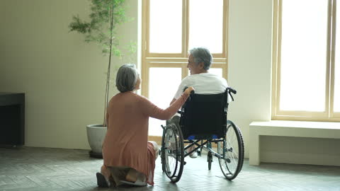 silver surfer generation - old man in wheelchair and old woman looking each other while smiling - silver surfer stock videos & royalty-free footage