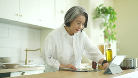 silver surfer generation - old woman looking recipe with tablet pc and cutting garlic - silver surfer stock videos & royalty-free footage