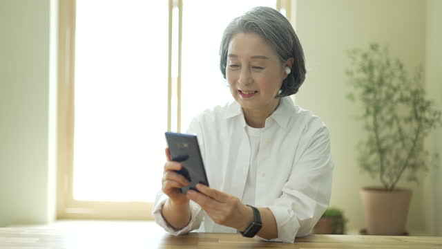 silver surfer generation - old woman wearing wireless earphone and using smart phone - silver surfer stock videos & royalty-free footage