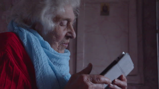 vídeos de stock e filmes b-roll de silver surfers. attractive active senior woman listening to music on her digital tablet. having fun while surfing on the net. - utilizar o tablet