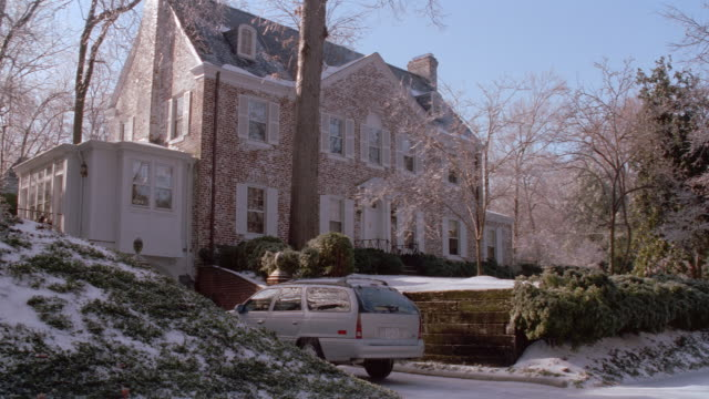 a silver suv sits in the driveway of a house in geogetown. - ostamerika stock-videos und b-roll-filmmaterial