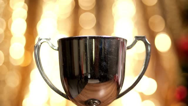 vídeos de stock e filmes b-roll de silver trophy with christmas light background, victory concept. - differential focus