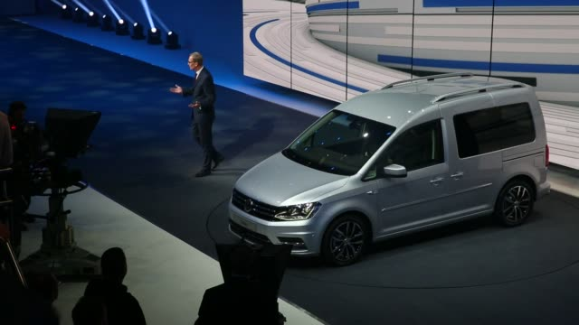 vídeos de stock e filmes b-roll de a silver volkswagen minivan arrives on stage during its unveiling at volkswagen ag's preshow event ahead of the 85th geneva international motor show... - plus key