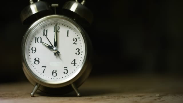 a silver-colored, metal, retro-style, analog alarm clock at 10:00 - clock stock videos & royalty-free footage