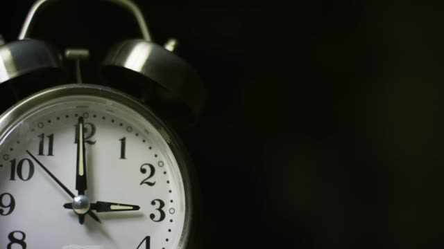 a silver-colored, metal, retro-style, analog alarm clock at 3:00 - number 3 stock-videos und b-roll-filmmaterial