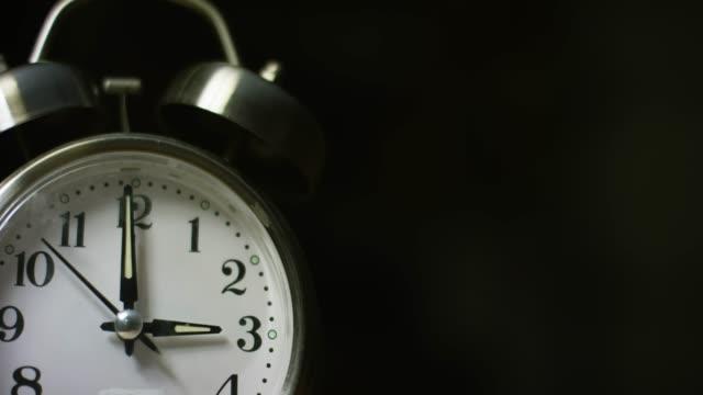 vídeos de stock, filmes e b-roll de a silver-colored, metal, retro-estilo, analógico relógio despertador em 3:00 - number 3