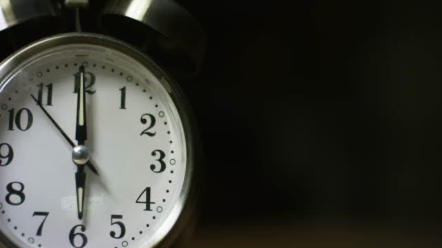 vídeos de stock, filmes e b-roll de a silver-colored, metal, retro-estilo, analógico relógio despertador em 6:00 - turning