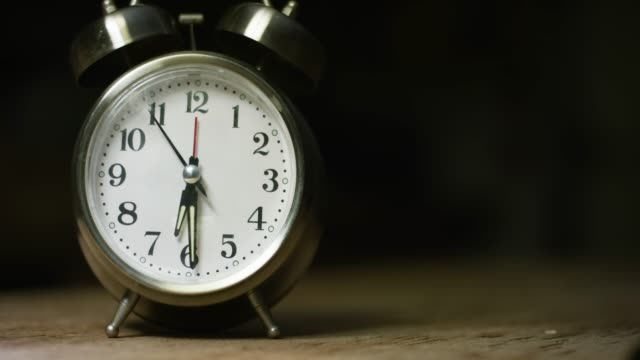 a silver-colored, metal, retro-style, analog alarm clock at 6:30 - 30 seconds or greater stock-videos und b-roll-filmmaterial
