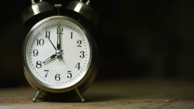 a silver-colored, metal, retro-style, analog alarm clock at 8:00 - decisions stock videos & royalty-free footage