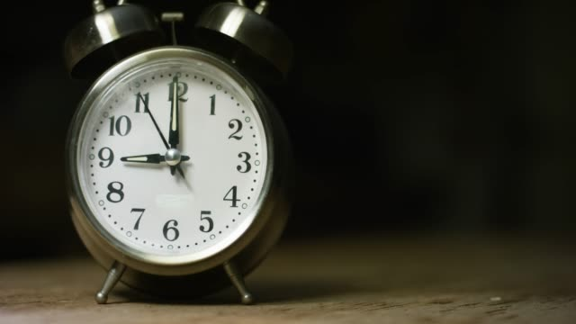 a silver-colored, metal, retro-style, analog alarm clock at 9:00 - silver coloured stock videos & royalty-free footage